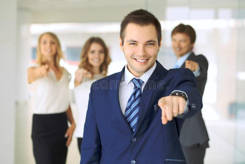 Hombre de negocios sonriente en oficina con los colegas en el fondo El señalar por el finger en la cámara foto de archivo libre de regalías