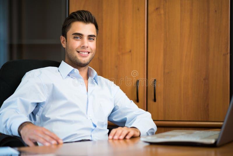 Hombre de negocios sonriente en su oficina imagenes de archivo