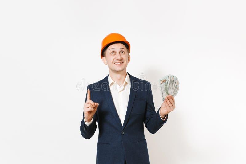 Hombre de negocios sonriente en traje oscuro, paquete protector de la tenencia del casco de protección de dólares, dinero del efe imagen de archivo