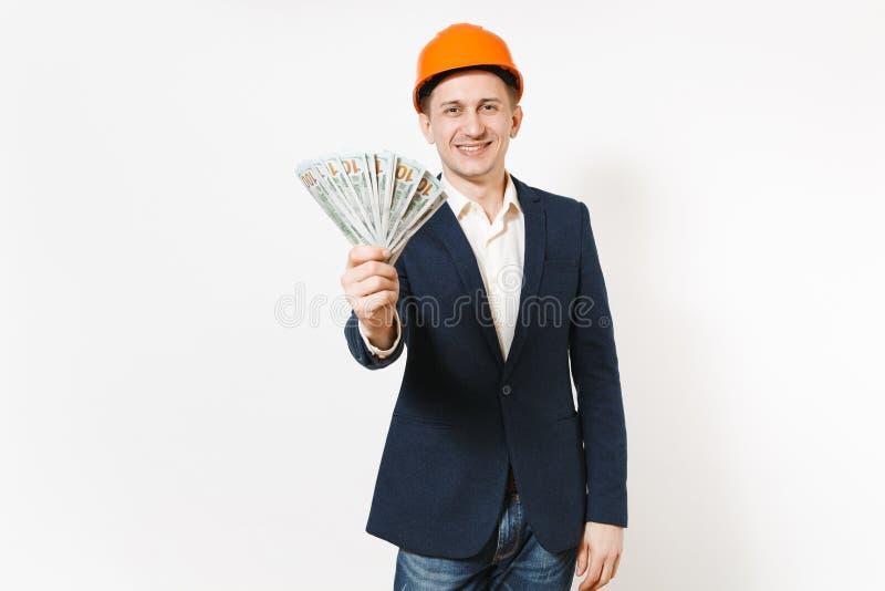 Hombre de negocios sonriente en traje oscuro, paquete protector de la tenencia del casco de protección de dólares, dinero del efe fotografía de archivo