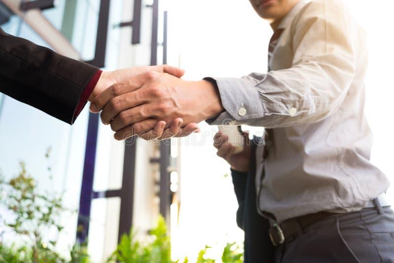 Hombre de negocios sonriente feliz que sacude las manos después de un acabamiento del trato fotografía de archivo