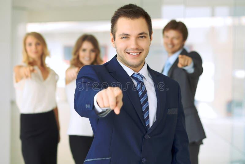 Hombre de negocios sonriente feliz y sus colegas que señalan por el finger en la cámara Concepto de patrón y de equipo del éxito fotografía de archivo libre de regalías