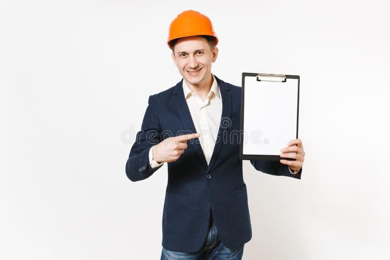 Hombre de negocios sonriente hermoso joven en el traje oscuro, casco de protección protector señalando el dedo índice en el table fotografía de archivo