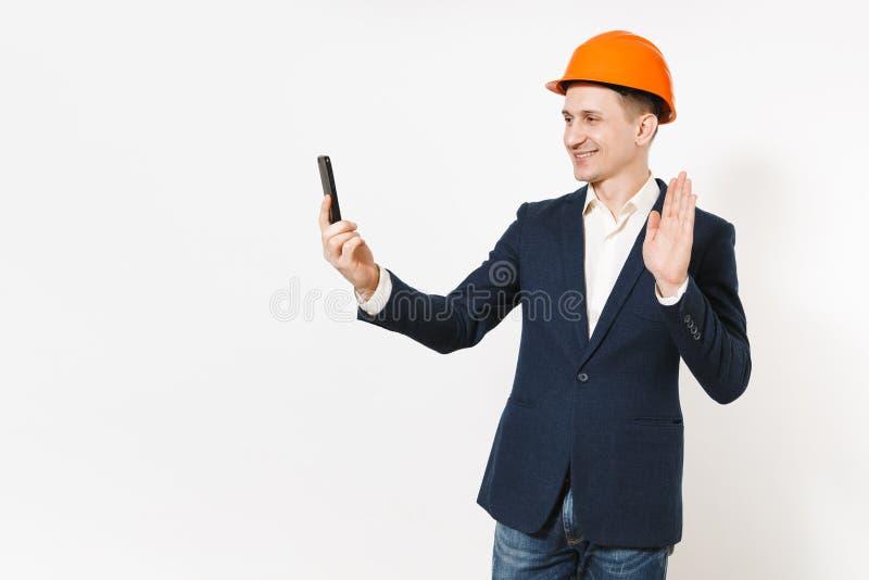 Hombre de negocios sonriente hermoso joven en el traje oscuro, casco protector de la construcción que hace el selfie en el teléfo imágenes de archivo libres de regalías