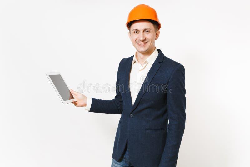 Hombre de negocios sonriente hermoso joven en el traje oscuro, ordenador protector de la PC de la tableta de la tenencia del casc imagen de archivo
