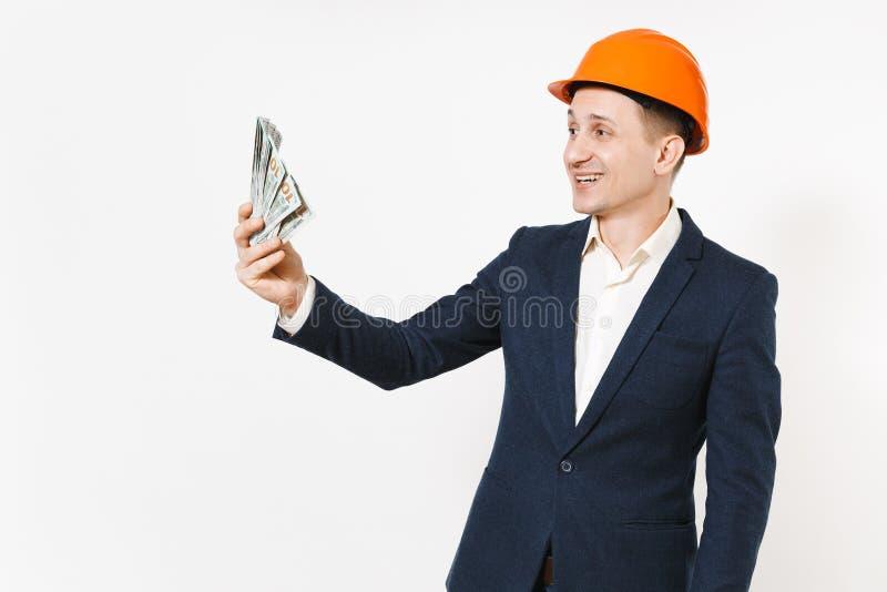 Hombre de negocios sonriente hermoso joven en el traje oscuro, paquete protector de dólares, dinero de la tenencia del casco de l fotografía de archivo libre de regalías
