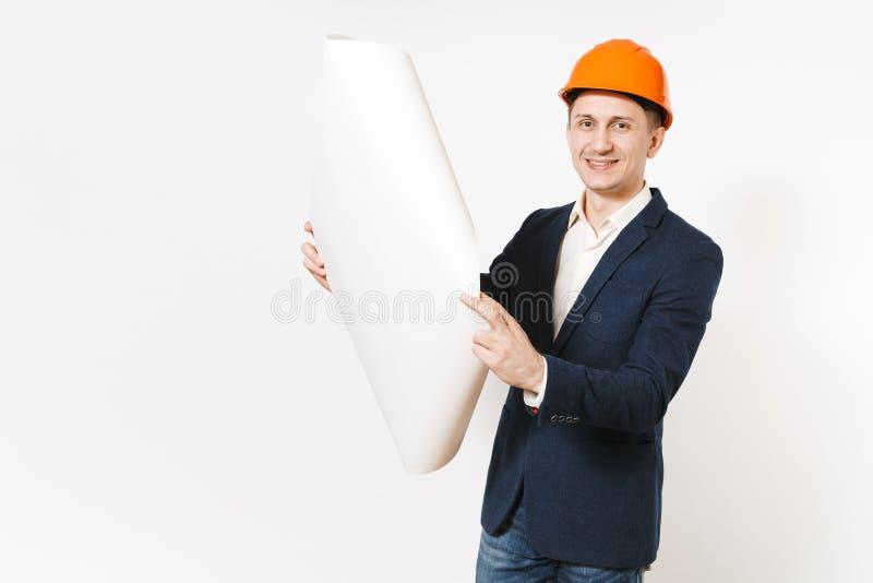 Hombre de negocios sonriente hermoso joven en el traje oscuro, plan del modelo del casco anaranjado protector de la construcción  imágenes de archivo libres de regalías
