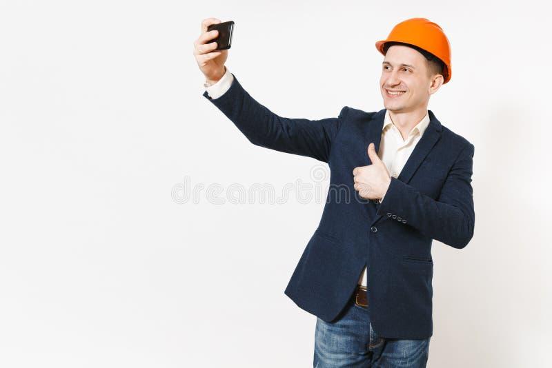 Hombre de negocios sonriente hermoso joven en el traje oscuro, pulgar protector de la demostración del casco de protección para a foto de archivo libre de regalías