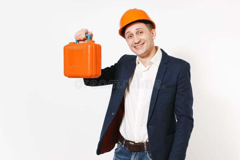 Hombre de negocios sonriente hermoso joven en traje oscuro, caso protector de la tenencia del casco de la construcción con los in fotografía de archivo libre de regalías