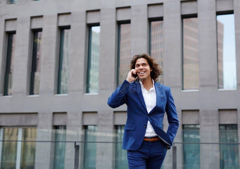 Hombre de negocios sonriente hermoso que habla en su teléfono móvil fotos de archivo libres de regalías
