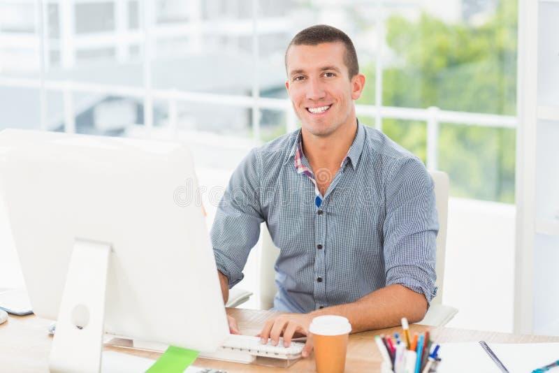 Hombre de negocios sonriente hermoso que mecanografía en un ordenador foto de archivo libre de regalías