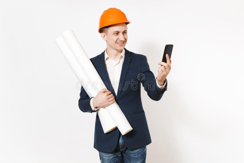 Hombre de negocios sonriente joven en el traje oscuro, casco de protección anaranjado protector que lleva a cabo planes de los mo foto de archivo