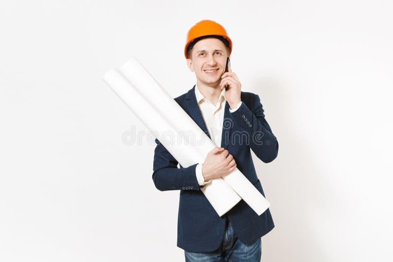 Hombre de negocios sonriente joven en el traje oscuro, casco de protección anaranjado protector que lleva a cabo planes de los mo fotografía de archivo