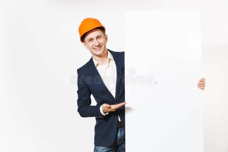 Hombre de negocios sonriente joven en el traje oscuro, el casco de protección protector llevando a cabo el material en blanco vac foto de archivo