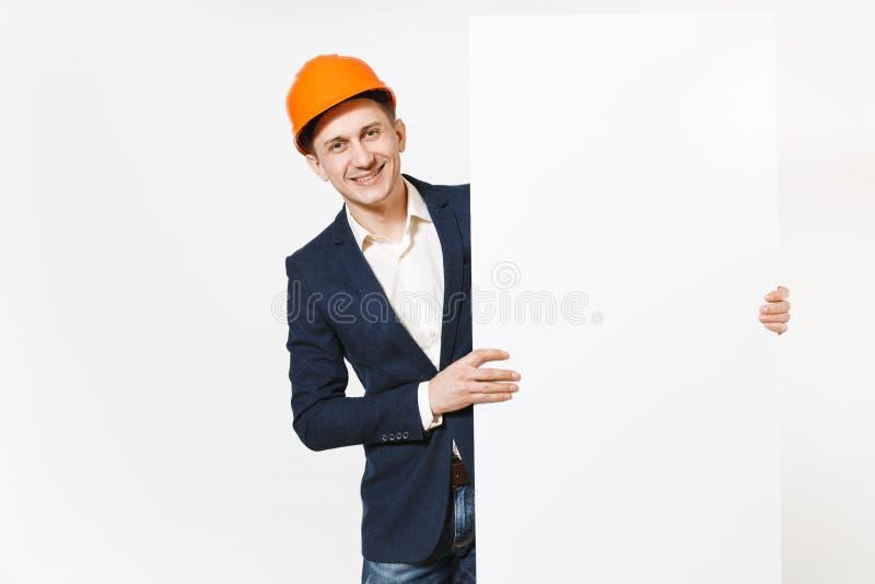 Hombre de negocios sonriente joven en el traje oscuro, casco de protección protector que lleva a cabo el material en blanco vacío foto de archivo