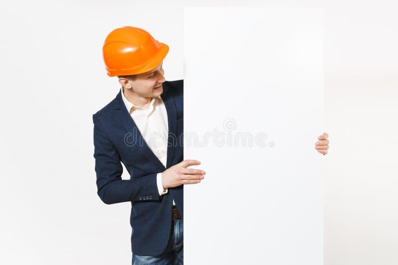 Hombre de negocios sonriente joven en el traje oscuro, casco de protección protector que lleva a cabo el material en blanco vacío fotos de archivo libres de regalías
