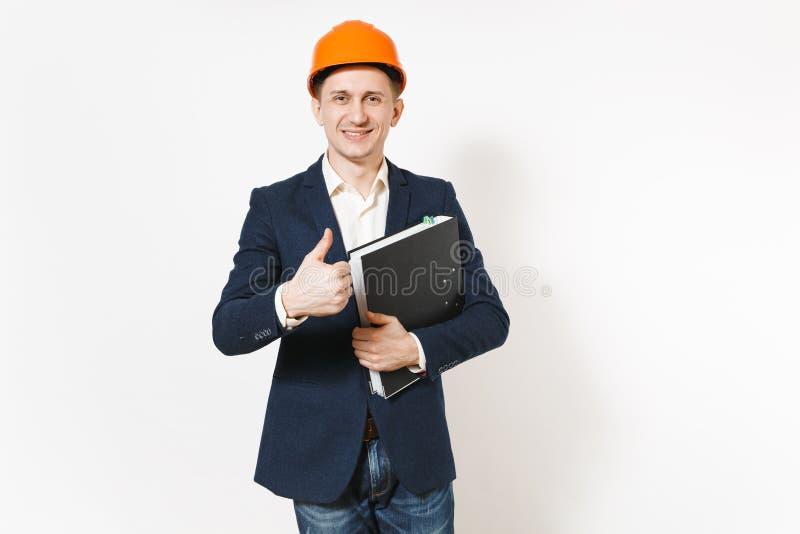 Hombre de negocios sonriente joven en el traje oscuro, casco de protección protector que sostiene la carpeta negra para el docume foto de archivo