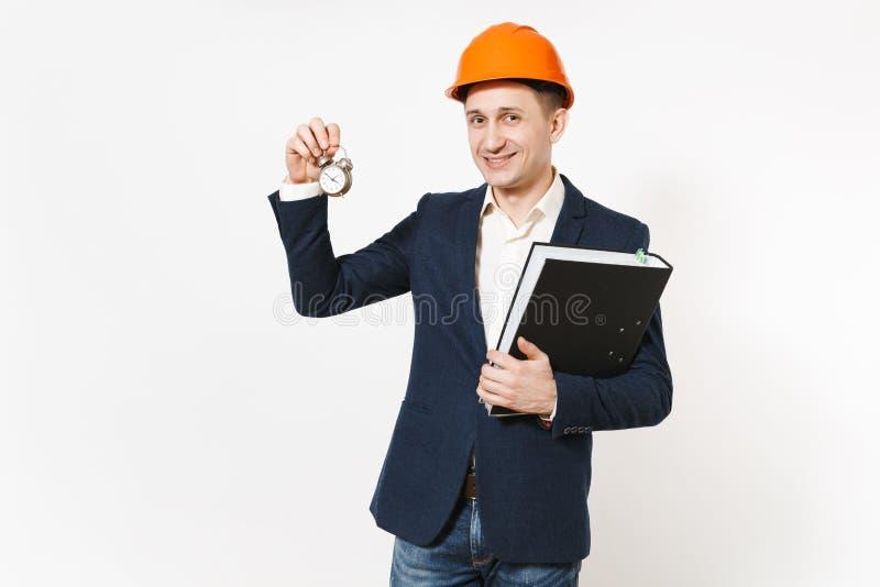 Hombre de negocios sonriente joven en el traje oscuro, el casco de protección protector sosteniendo la carpeta negra para el docu imágenes de archivo libres de regalías
