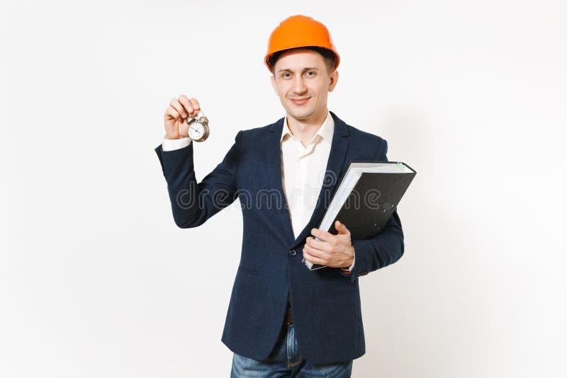 Hombre de negocios sonriente joven en el traje oscuro, el casco de protección protector sosteniendo la carpeta negra para el docu imagen de archivo