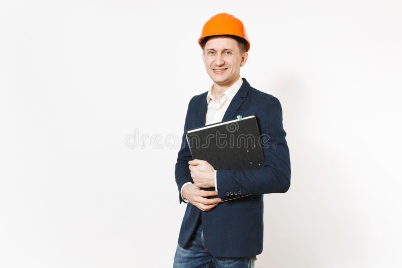 Hombre de negocios sonriente joven en el traje oscuro, casco protector de la construcción que sostiene la carpeta negra para el d fotografía de archivo libre de regalías