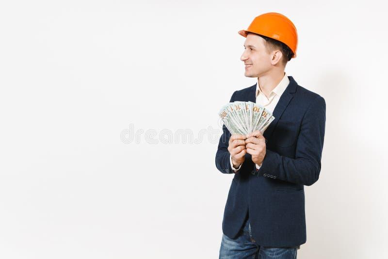 Hombre de negocios sonriente joven en el traje oscuro, paquete protector de dólares, dinero de la tenencia del casco de la constr fotografía de archivo libre de regalías