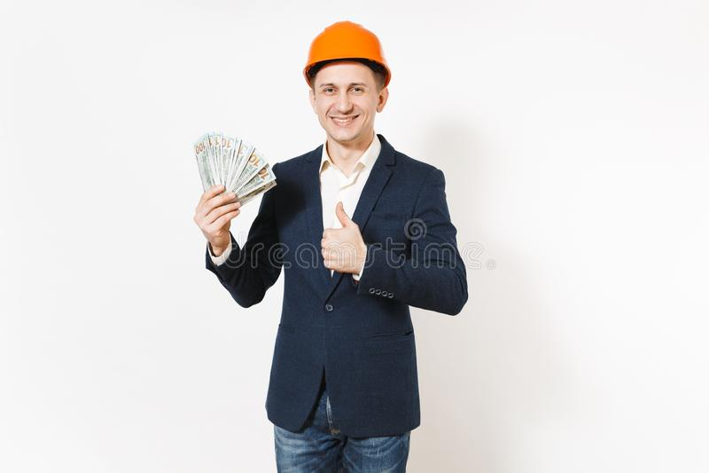Hombre de negocios sonriente joven en el traje oscuro, paquete protector de la tenencia del casco de protección de dólares, diner imagenes de archivo