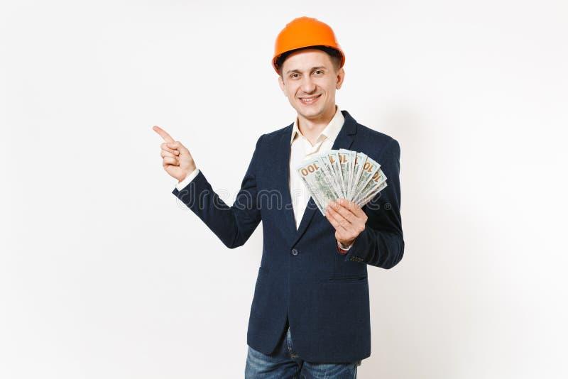 Hombre de negocios sonriente joven en el traje oscuro, paquete protector de la tenencia del casco de protección de dólares, diner imagen de archivo