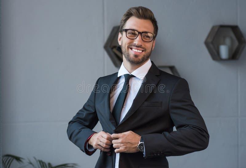 Hombre de negocios sonriente joven en los vidrios que abotonan encima de a imágenes de archivo libres de regalías
