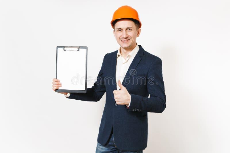 Hombre de negocios sonriente joven en traje oscuro, tablero anaranjado protector de la tenencia del casco de protección con la ho fotografía de archivo