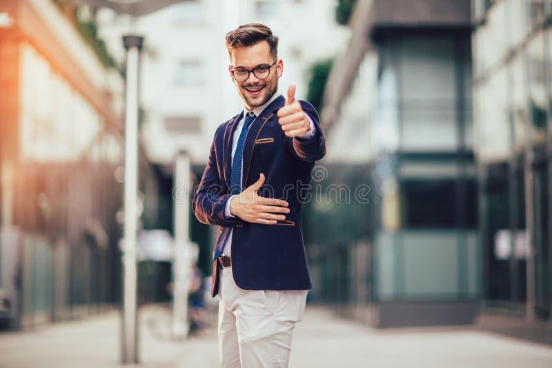 Hombre de negocios sonriente joven moderno que da el pulgar encima de al aire libre fotos de archivo libres de regalías