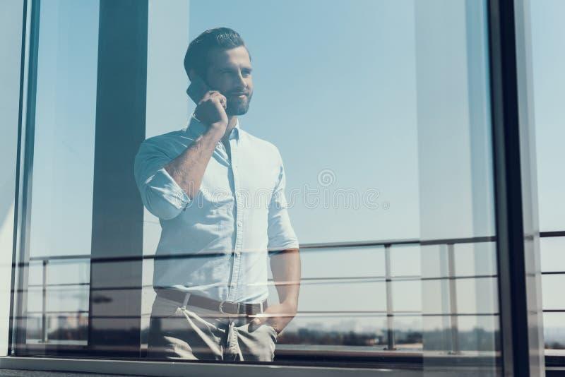 Hombre de negocios sonriente joven que habla en el teléfono foto de archivo libre de regalías
