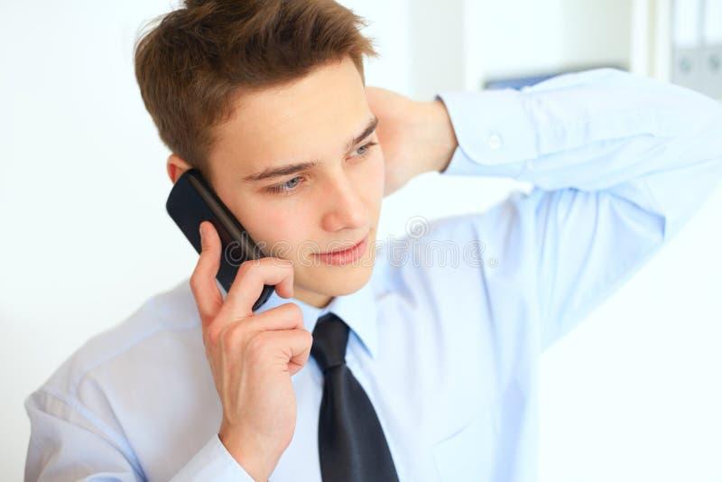 Hombre de negocios sonriente joven que habla en el teléfono celular foto de archivo