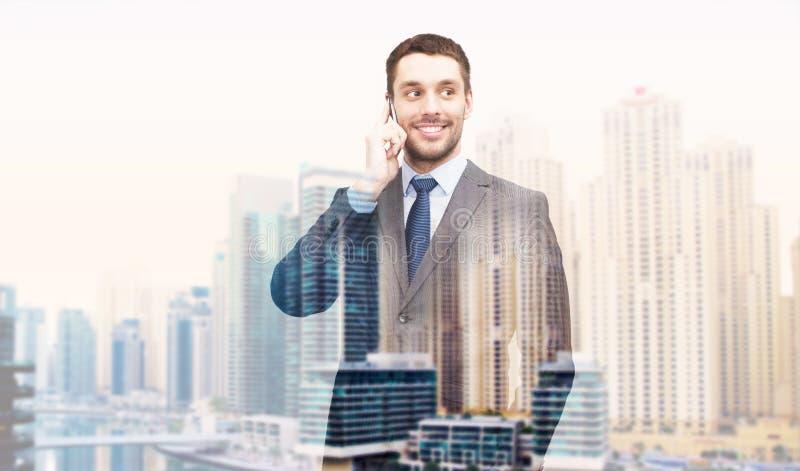 Hombre de negocios sonriente joven que invita a smartphone imagen de archivo libre de regalías