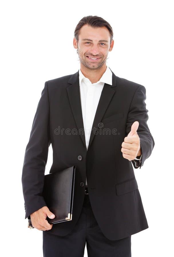 Hombre de negocios sonriente joven que muestra los pulgares para arriba fotos de archivo