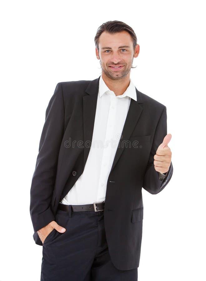 Hombre de negocios sonriente joven que muestra los pulgares para arriba imágenes de archivo libres de regalías