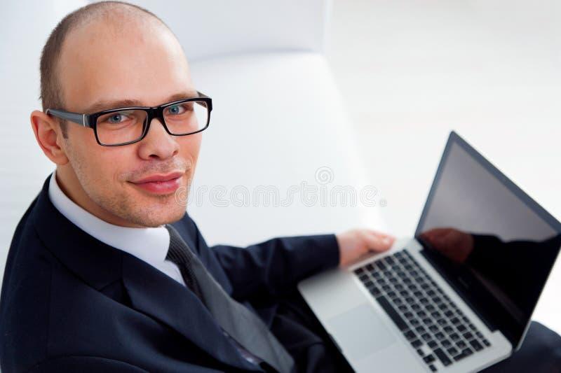 Hombre de negocios sonriente joven que se sienta con el ordenador portátil fotos de archivo libres de regalías
