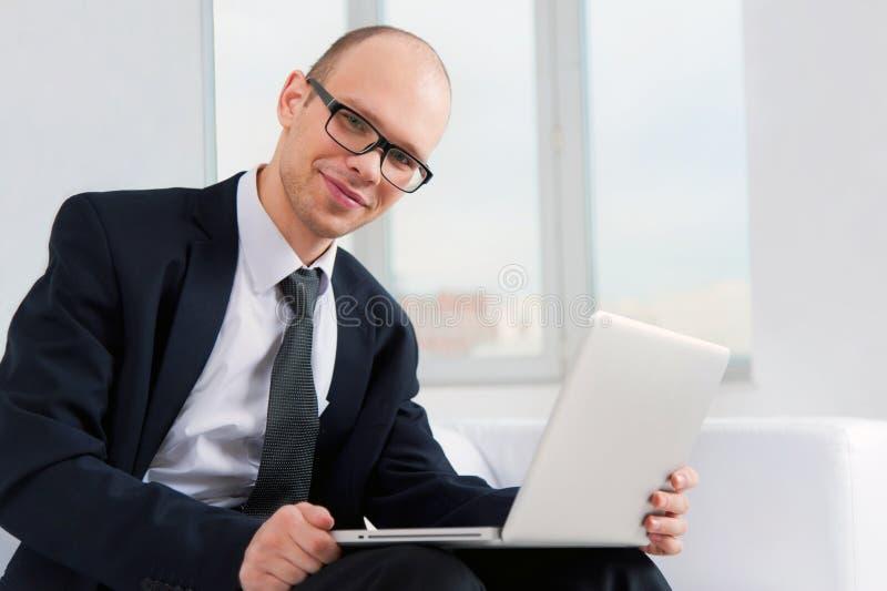 Hombre de negocios sonriente joven que se sienta en el sofá con el ordenador portátil fotografía de archivo