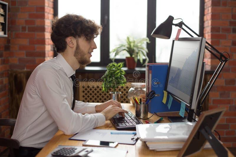 Hombre de negocios sonriente joven que trabaja en el ordenador imágenes de archivo libres de regalías