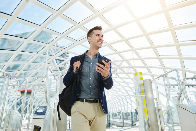 Hombre de negocios sonriente por el torniquete del aeropuerto con el teléfono móvil imagen de archivo