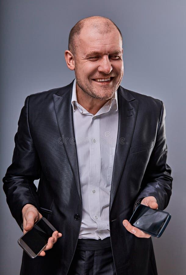 Hombre de negocios sonriente positivo que habla en dos tel?fonos m?viles muy emocionales en traje de la oficina en fondo gris del fotografía de archivo