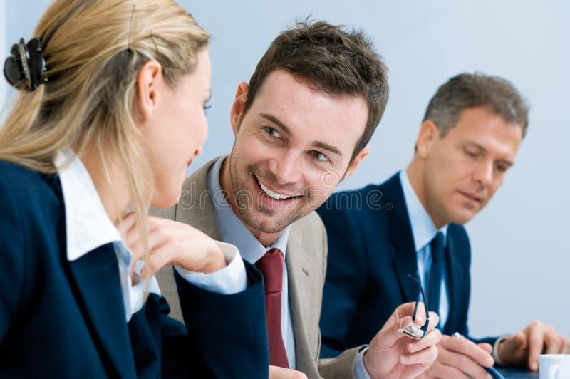 Hombre de negocios sonriente que habla con los colegas imagen de archivo