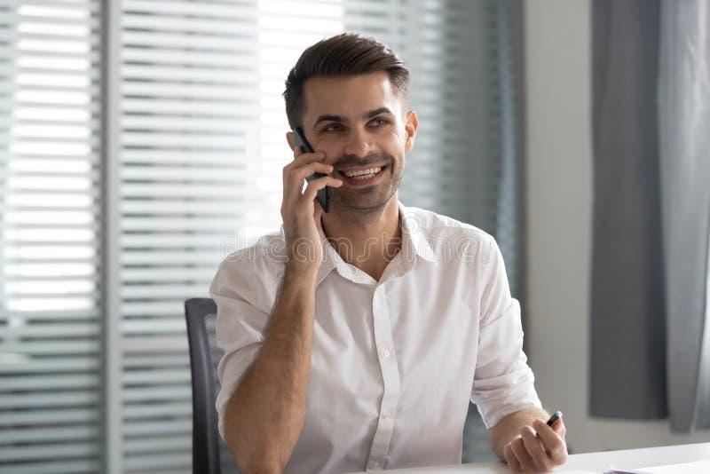 Hombre de negocios sonriente que habla en el teléfono que hace llamada del negocio en oficina fotos de archivo