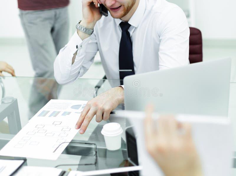 Hombre de negocios sonriente que habla en el tel?fono que se sienta en su escritorio imagen de archivo libre de regalías