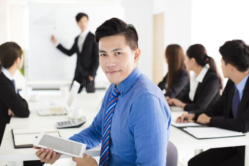 Hombre de negocios sonriente que mira la cámara con el colega imagen de archivo