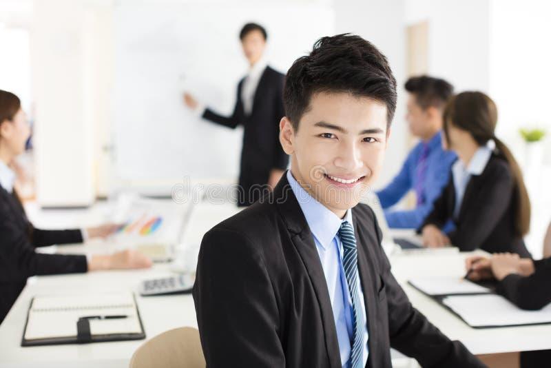 Hombre de negocios sonriente que mira la cámara con el colega fotografía de archivo