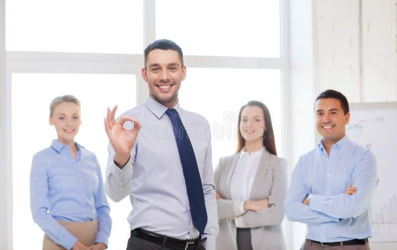 Hombre de negocios sonriente que muestra la aceptable-muestra en oficina fotos de archivo