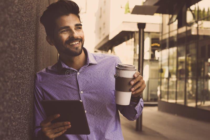 Hombre de negocios sonriente que se inclina contra la pared con la tableta digital MA imagenes de archivo