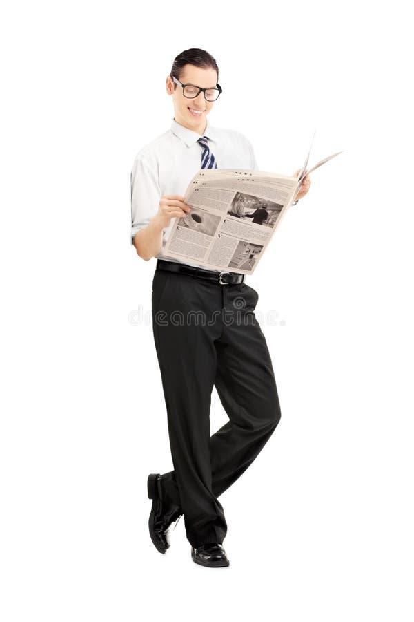 Hombre de negocios sonriente que se inclina contra la pared y la lectura de un periódico imagenes de archivo