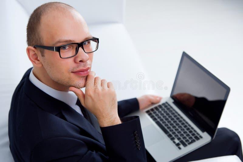 Hombre de negocios sonriente que se sienta con el ordenador portátil foto de archivo libre de regalías