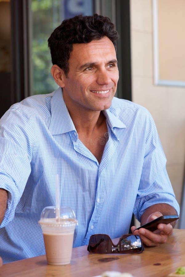 Hombre de negocios sonriente que se sienta con el teléfono móvil imágenes de archivo libres de regalías